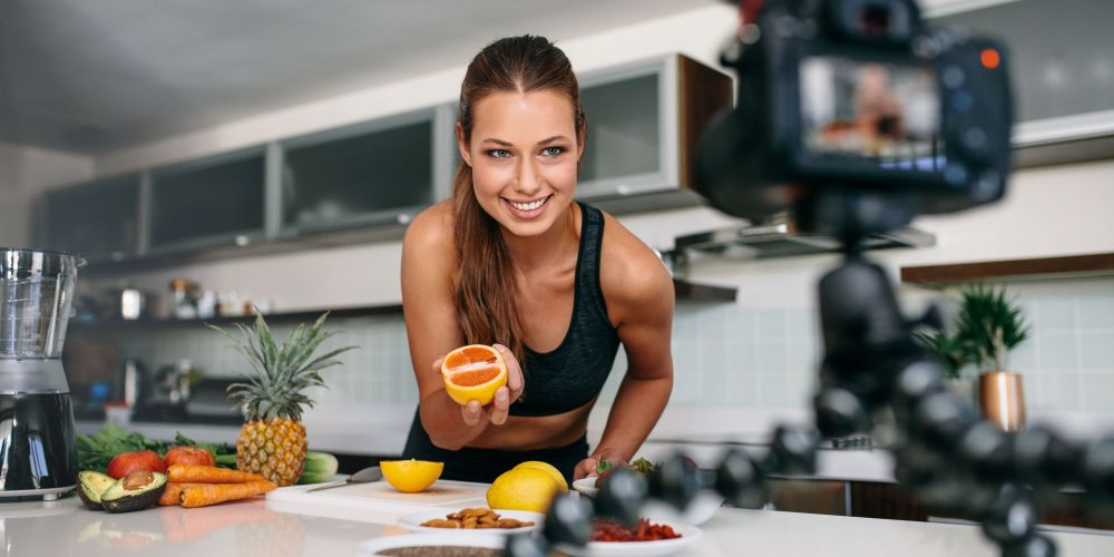 attractive_young_female_brunette_blogger_vlogger_social_media_influencer_recording_filming_health_cooking _itness_content_camera_production_smiling_yellow
